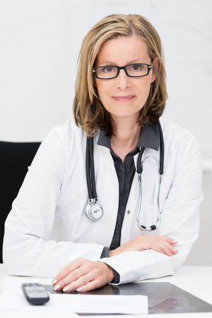 Attractive middle-aged female doctor wearing glasses and a stethoscope sitting at her desk looking directly at the camera with a smile