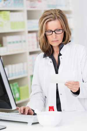 pharmacist: Middle-aged female pharmacist at work standing at the computer on the pharmacy counter checking a prescription with a serious expression Stock Photo