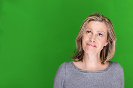 mid adults: Playful attractive middle-aged woman standing thinking looking up into the air with a whimsical mischievous expression on green with copyspace