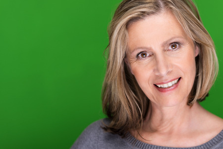 Sincere concerned attractive middle-aged woman with shoulder length blond hair looking directly at the camera with a smile, on green with copyspace