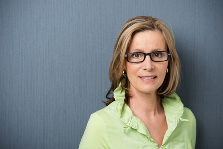 Elegant middle-aged woman in glasses looking directly at the camera with a friendly smile and interested expression, on grey with copyspace Stock Photo