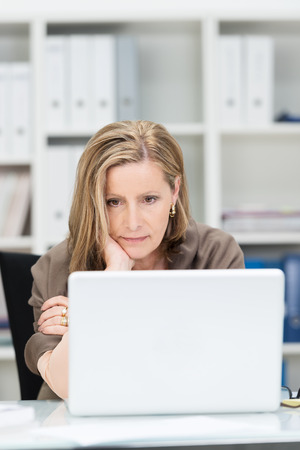 concentrates: Businesswoman staring glumly at her laptop computer as she concentrates on information on the screen Stock Photo