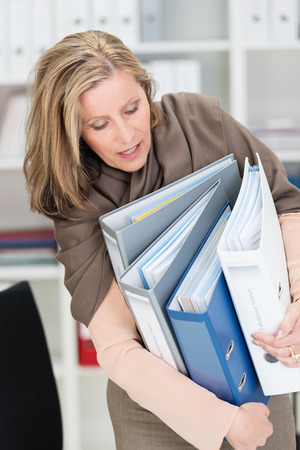 armful: Frustrated attractive middle-aged businesswoman struggling with an armful of office files as they fall all over the place a she tries to move them Stock Photo