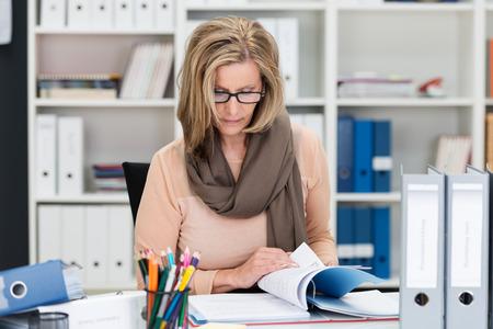 Hardwerkende zakenvrouw zich te concentreren op haar werk als ze zit paging door een bindmiddel papierwerk op haar bureau in het kantoor