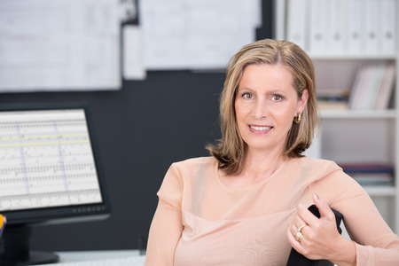 attractive office: Middle-aged businesswoman sitting at her desk turning with her arm over the back of her office chair to smile at the camera
