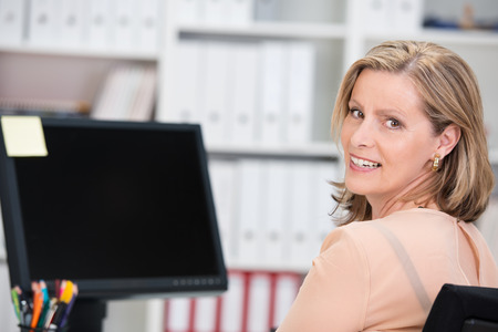 Smiling successful businesswoman sitting at her desk in the office in front of a desktop monitor turning to give the camera a happy smile Stock Photo