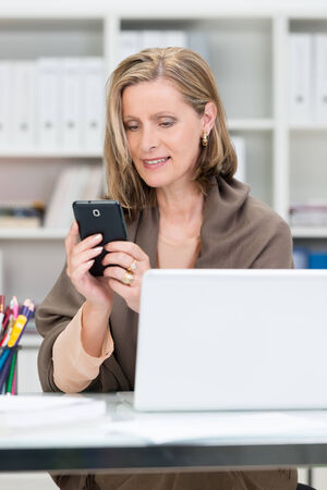 Attractive middle-aged businesswoman sitting at her desk reading an sms message on her mobile phone photo