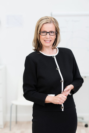 professor: Attractive businesswoman dressed in black wearing glasses standing with clasped hands smiling at the camera Stock Photo