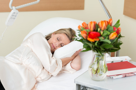 surgery bed: Attractive middle-aged female patient lying sleeping peacefully in a hospital bed as she recuperates from an injury, surgery or illness
