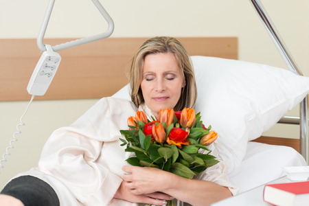 Sad middle-aged woman with downcast eyes clutching a bunch of roses to her chest as she lies in bed in hospital
