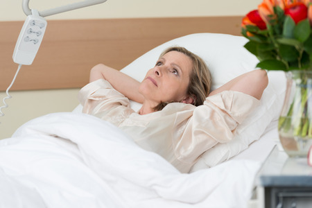 injured woman: Worried middle-aged woman lying thinking in a hospital bed with her hands clasped behind her head as she stares at the ceiling with an intense expression