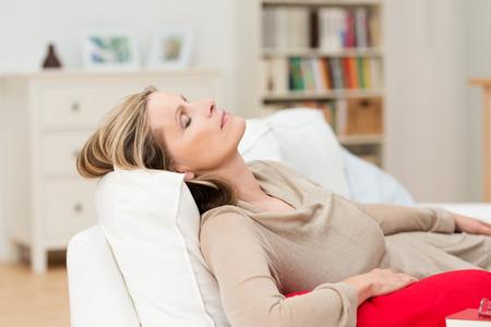 mujer descansando: Mujer que tiene una siesta en el sof� de relax con su cabeza inclinada hacia atr�s en el coj�n y los ojos cerrados