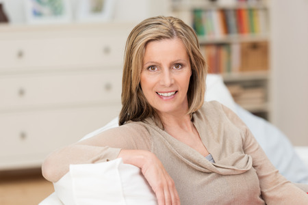 Smiling attractive middle-aged blond woman sitting in a relaxed position with her arm over the back on a sofa in her living room smiling at the camera Stock Photo
