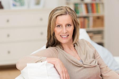 Sonrisa atractiva mujer rubia de mediana edad sentado en una posición relajada con su brazo sobre el respaldo de un sofá de su sala de estar sonriendo a la cámara Foto de archivo - 28204256