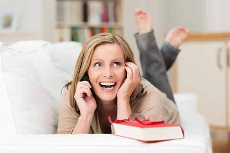 one mature woman only: Attractive middle-aged woman lying on her stomach on a sofa laughing as she chats on her mobile phone Stock Photo