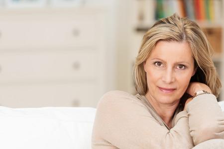 魅力的な誠実な中年女性は真剣な表情でカメラを直接見て上げられた腕に彼女の頭をもたれソファーに座っていた