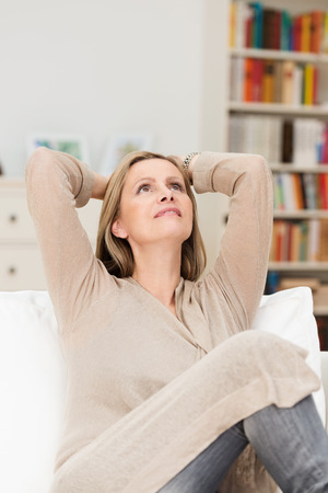tilted: Pretty middle-aged woman sitting daydreaming on a sofa in her living room with her head tilted back and hands clasped behind her head