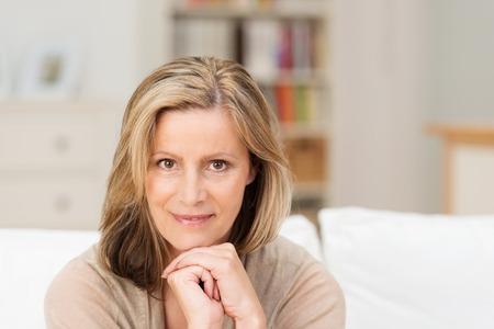mujer pensativa: Hermosa amistad mujer de mediana edad sentado mirando directamente a la cámara con una sonrisa y con la barbilla apoyada en las manos cruzadas