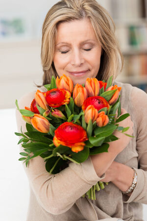 Attractive middle-aged woman hugging a bunch of fresh orange flowers to her chest and smiling with contentment and pleasure Stock Photo