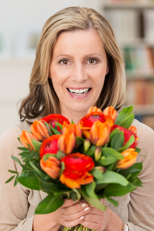 middle easter: Happy smiling woman holding a gift of fresh orange flowers in a large bouquet on her birthday, Mothers Day, anniversary or Valentines