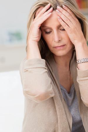 頭痛と彼女の目と彼女の寺院に彼女の手を繋いでいるストレスに苦しむ女性は痛みで閉鎖 写真素材