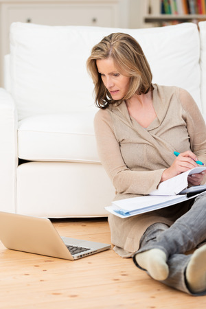 boomer: Woman doing her work at home on a laptop computer sitting relaxing on the floor of the living room with a large binder of notes on her lap