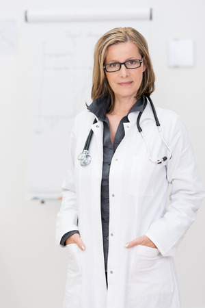 Confident friendly female doctor standing smiling at the camera with her hands in the pockets of her lab coat Stock Photo