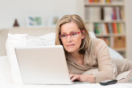 Vrouw draagt een bril liggend op een sofa thuis concentreren als ze werkt op een laptop Stockfoto