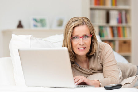 silver surfer: Middle-aged woman relaxing at home with her laptop computer lying on her stomach on a sofa smiling at the camera Stock Photo