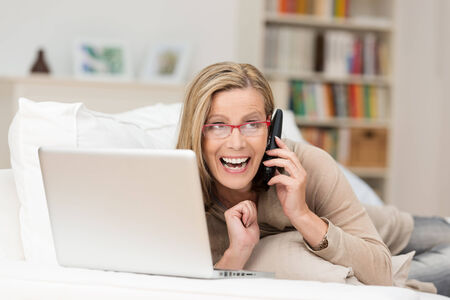 chats: Vivacious woman laughing as she chats on her mobile phone while relaxing at home with a laptop computer