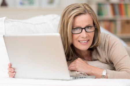 quizzical: La mujer llevaba gafas de trabajo en casa en su computadora port�til recling en un sof� haciendo una pausa para mirar a la c�mara con una expresi�n burlona ans peque�a sonrisa
