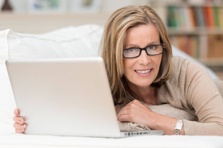 Woman wearing glasses working at home on her laptop computer recling on a sofa pausing to look at the camera with a quizzical expression ans small smile photo