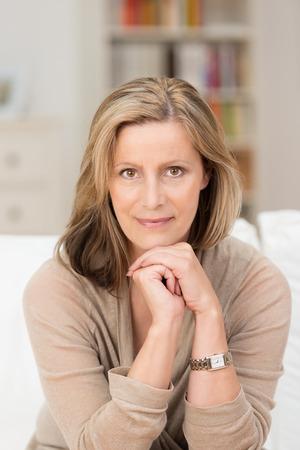 mujer alegre: Retrato de una hermosa amigable mujer de mediana edad sentado en un sof� en casa descansando el ment�n en las manos mirando a la c�mara con una sonrisa