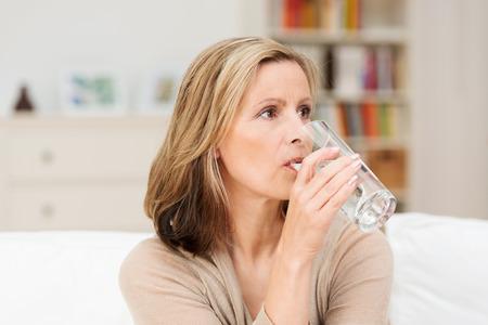 彼女は、自宅でソファに座っていると冷たい新鮮な水のさわやかな健全なガラスを飲んでのどが渇いている女性が深刻な表情で遠くを見つめる