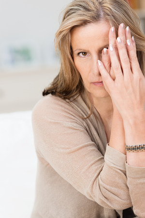 Woman peering out from behind her hands looking at the camera with a serious withdrawn expression photo