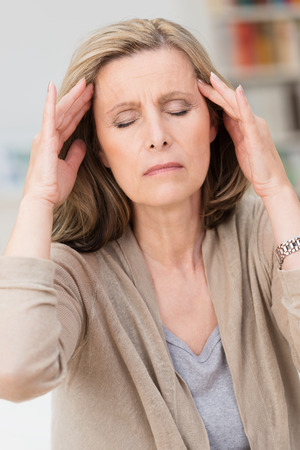 Middle-aged woman with a migraine headache sitting with her fingers to her temples and eyes closed in pain as she tries to relax