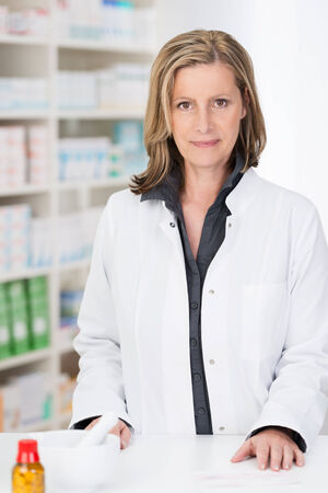 stocked: Attractive female pharmacist standing behind the counter in her pharmacy looking at the camera with a smile against a backdrop of stocked shelves