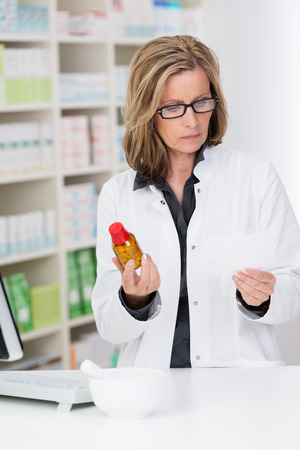 Attractive middle-aged female pharmacist checking a prescription against a bottle of tablets in her hand as she stands working at the counter in the pharmacy photo