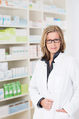 hand in pocket: Attractive friendly woman pharmacist wearing glasses standing with her hand in the pocket of her white coat against stocked shelves smiling at the camera
