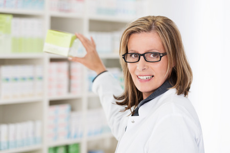 Middle-aged female pharmacist wearing glasses removing tablets off the shelf and turning to look at the camera photo