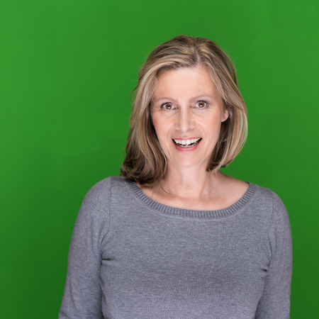 Beautiful middle-aged woman with a lovely smile standing against a green background with copyspace looking at the camera