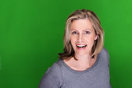 vejez feliz: Emocionado atractiva mujer de mediana edad de pasar hacia la cámara con una sonrisa de alegría sobre un fondo verde con copyspace Foto de archivo