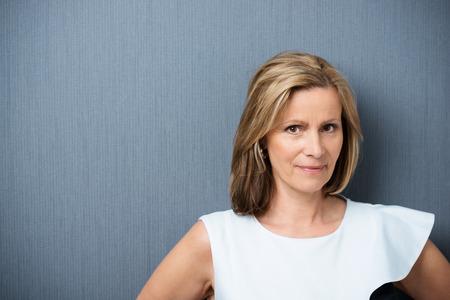 Aantrekkelijke middelbare leeftijd blonde vrouw kijkt naar de camera met een speculatieve look en een schijnbeweging glimlach van wantrouwen tegen een donkere grijze achtergrond met copyspace