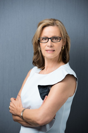 one mature woman only: Serious confident middle-aged woman wearing spectacles standing with her arms crossed looking intently at the camera