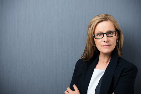 Scholarly looking middle-aged woman wearing heavy rimmed glasses and a black jacket standing with folded arms looking at the camera with a serious expression photo