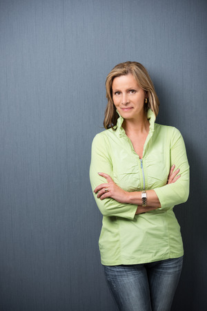 Confident relaxed trendy middle-aged woman leaning against a grey background with folded arms smiling at the camera photo