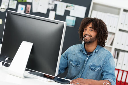 Friendly charismatic hip young African American businessman in a casual denim shirt sitting at his desktop computer in the office smiling at the camera photo