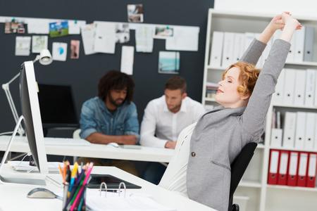 working woman: Felice bella giovane imprenditrice contento di relax nella sua poltrona allungando le braccia in aria in un ufficio occupato con multietnici business partner di sesso maschile