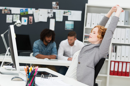 contented: Happy beautiful contented young businesswoman relaxing in her chair stretching her arms in the air in a busy office with multiethnic male business partners