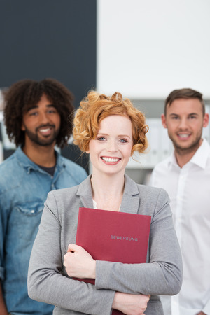 job qualifications: Successful beautiful stylish young female job applicant clasping her CV to her chest and posing in front of two multiethnic young businessmen with a beaming smile Stock Photo